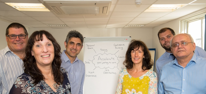 The Accelerate team stand in front of a display board