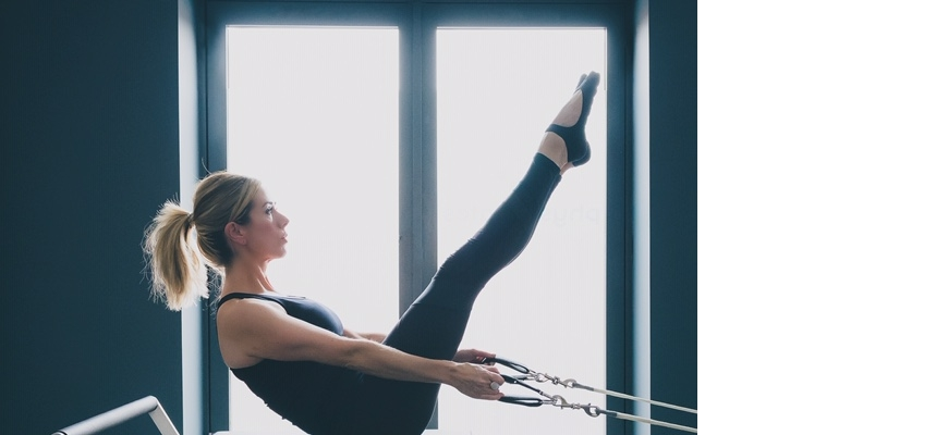 A woman practices Pilates-led physiotherapy