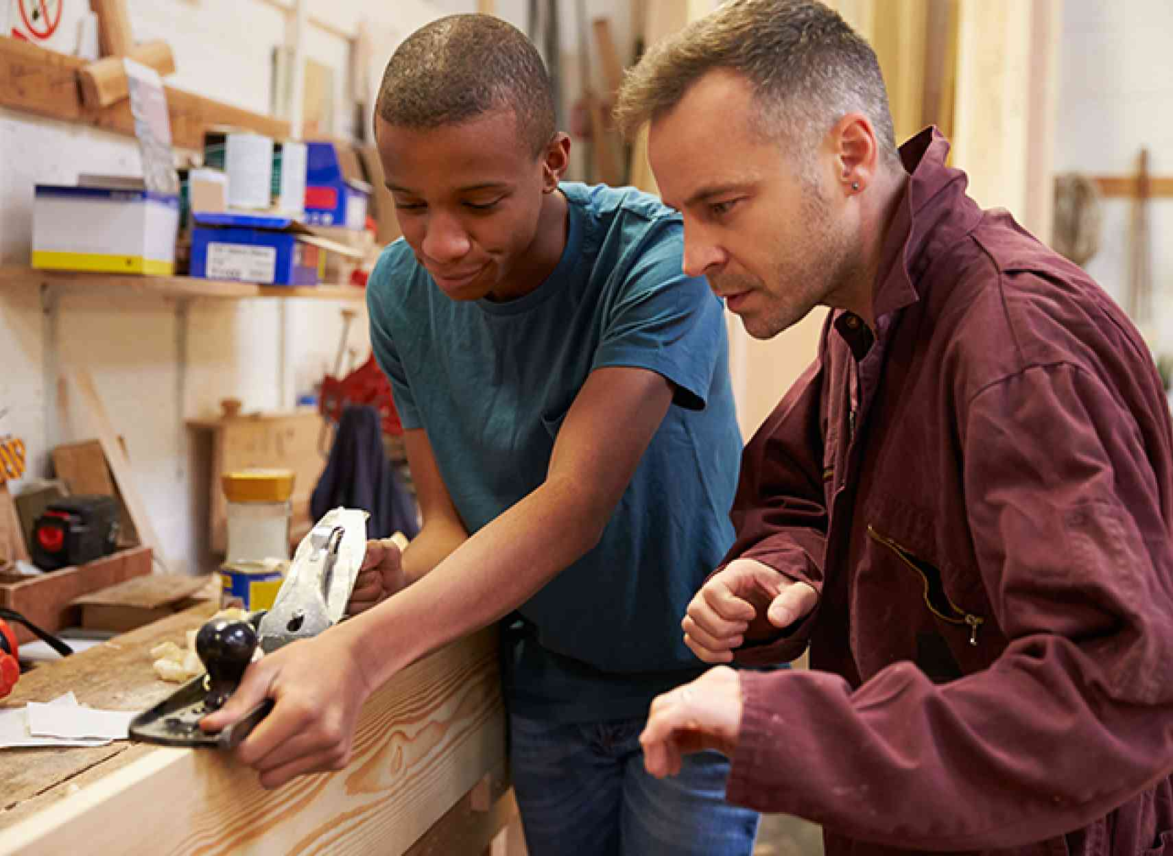Teacher training young man at woodwork