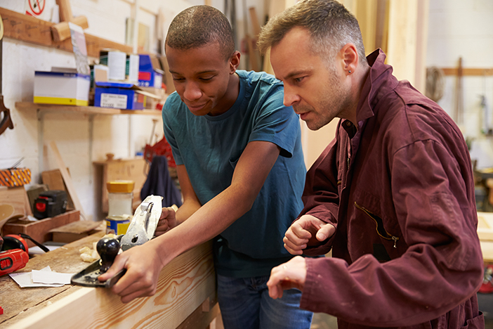 Teacher training young man at woodwork